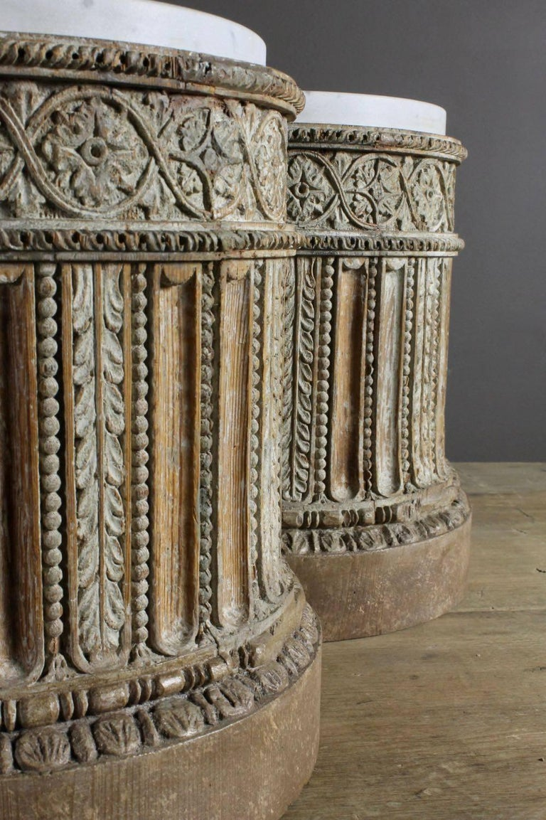 A pair of intricately carved 18th century English pine pedestal bases with traces of original gesso and original inset carrara marble tops. Circa 1780. Originally, these pedestals were covered in gilt and, at some point, that decoration has been