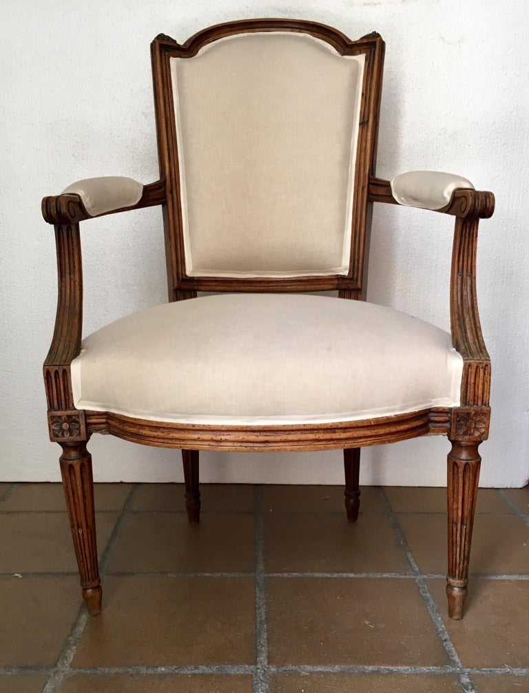 Pair of armchairs or fauteuils, Luis XVI, late 18th century, in walnut wood with back sculpted in guilloche, on fluted tapering legs, the interior has been reinforced and restored, upholstery.
