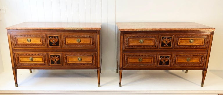 Pair of marble top two drawer commodes with mahogany, ebony, satinwood and walnut inlay. This Pair of commodes are in the manner of Giuseppe Maggiolini. The commodes are elegantly inlaid. The classic design with the drawers having a center inlaid