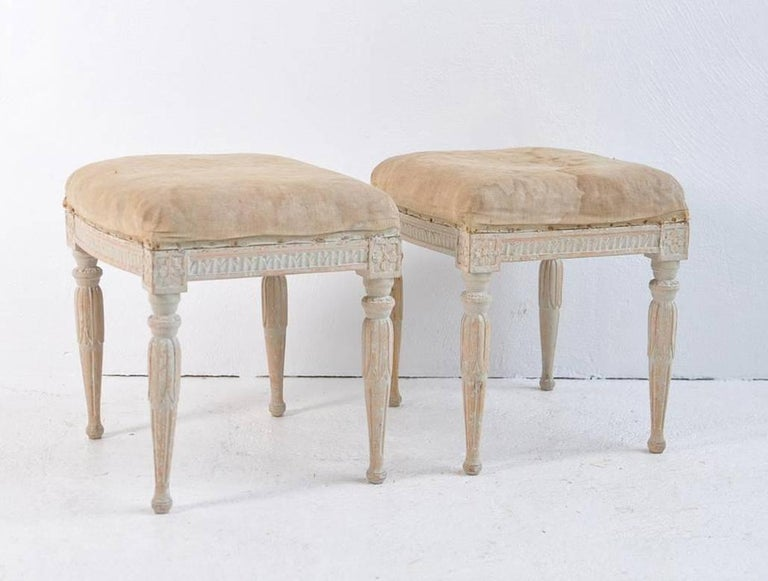 A pair of Swedish Gustavian stools by Erik Holmberg, chair maker in Stockholm between 1791-1796. Signed EHB. This charming pair has been hand-scraped to reveal the original paint. Carved egg and dart detail around the seat frame with carved rosettes