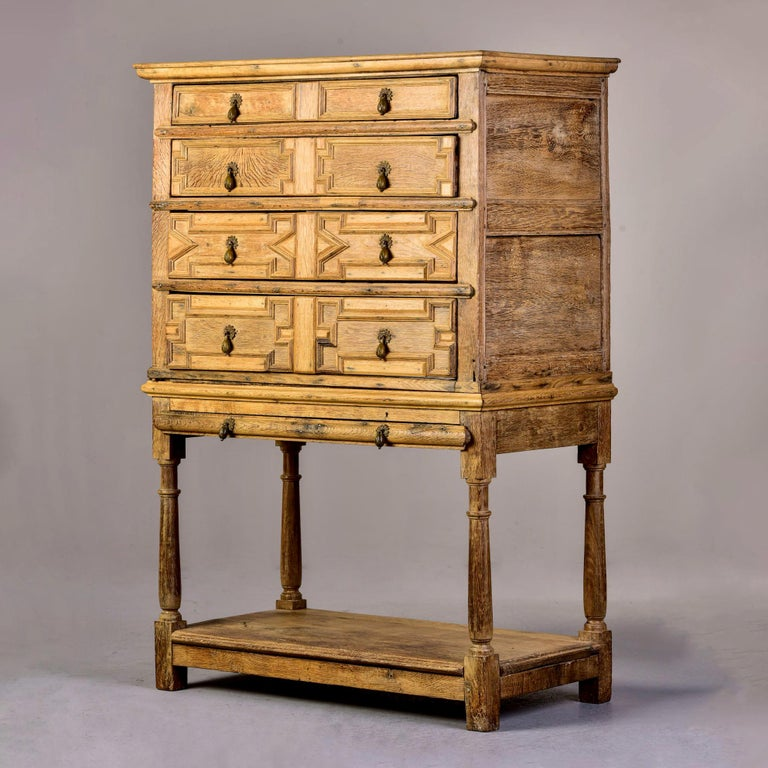 Circa 1780s English four drawer chest on stand in pale oak with original brass drop pulls in form of flower bud. Lower pull out shelf, carved details on drawer fronts. Some evidence of former/inactive wormholes and some drawer bottoms have