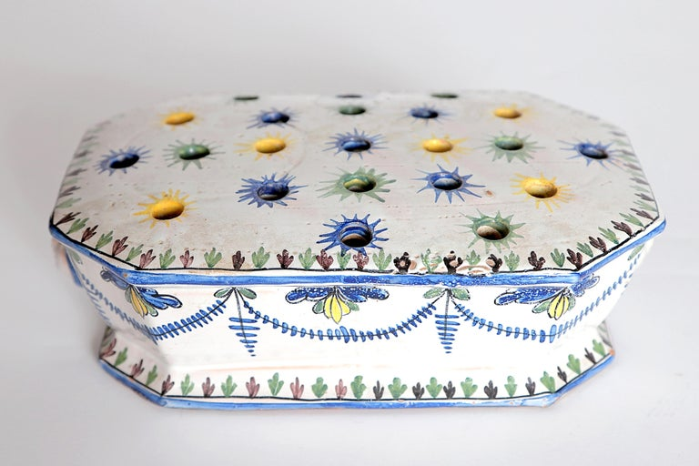 A faience flower frog, white ground with decoration in blue, yellow, and green, swags decorate the front, back, and sides of the piece, applied masks (faces) each end, starbursts painted around the holes.