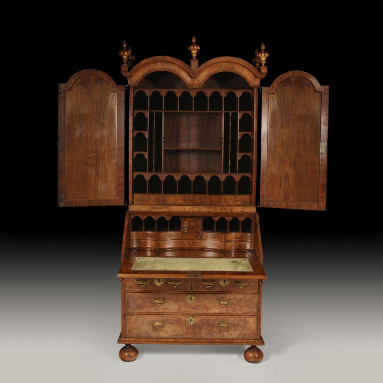 A Queen Anne fully fitted figured-walnut double dome bureau bookcase, circa 1710