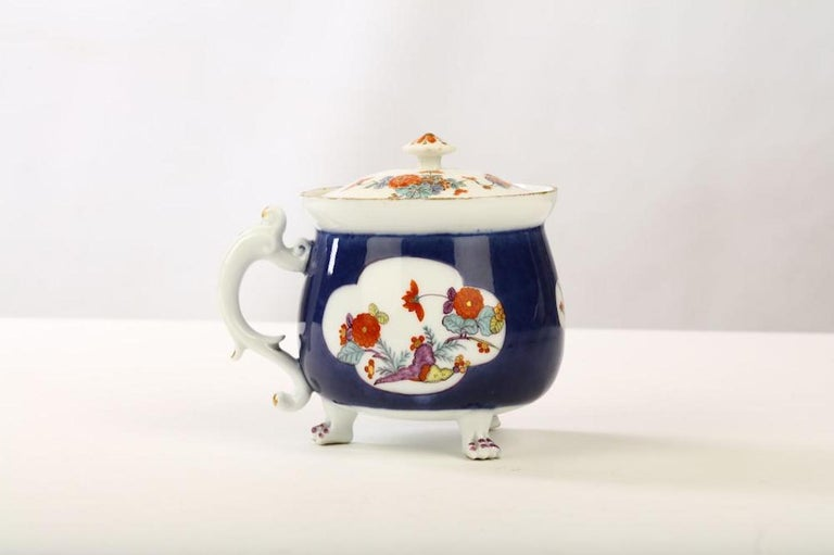 rare meissen underglaze-blue-ground cream pot and a cover, circa 1730, on three paw feet picked out in puce, the sides reserved with three quatrelobe panels painted in Kakiemon style with indianische Blumen, the scroll handle with further flowers,