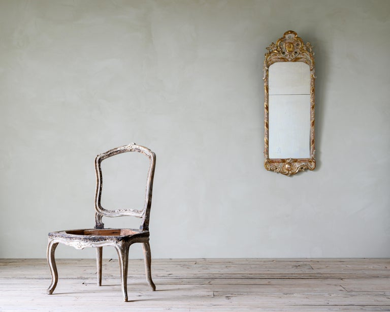 18th century Swedish giltwood mirror from the Rococo period, circa 1770.   The condition is fair with traces of the original gilt, historical restorations. No issues with the structure.
