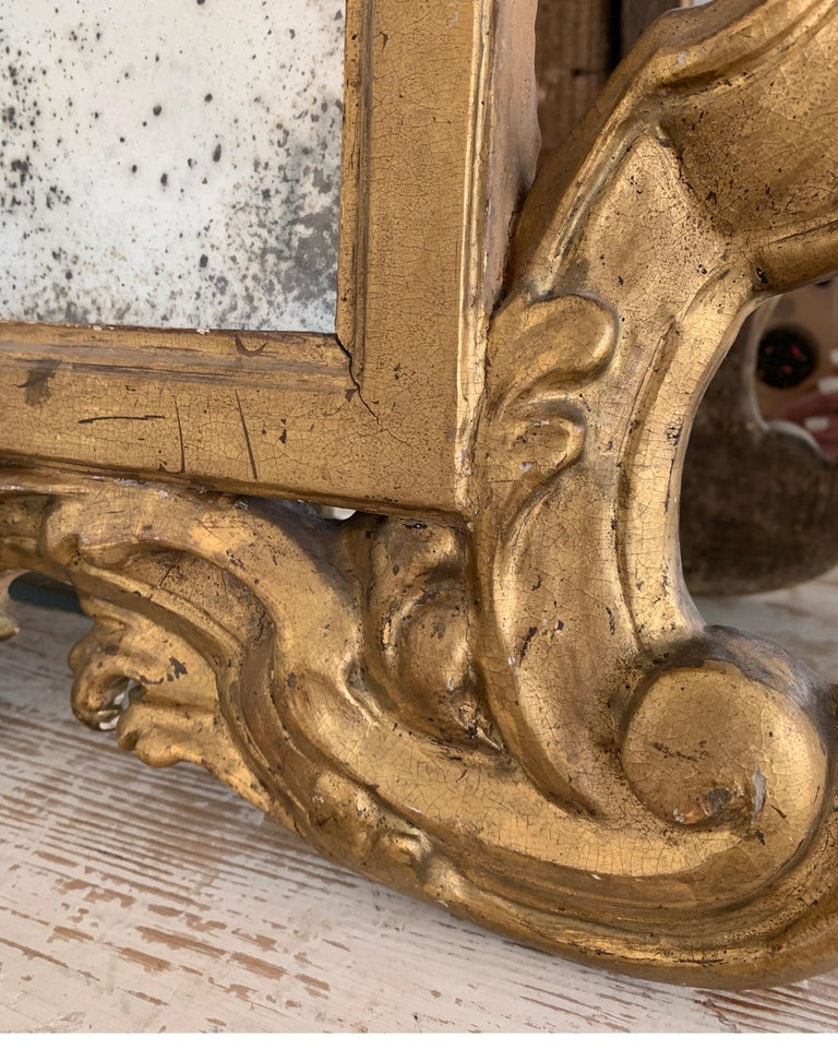 Incredible, rare, small size Rococo gold gilt pair of carved wood mirrors. These are so much more impressive in person. The original gold gilt is amazing as it the old glass. They are terrific over demi-tables, or chests.