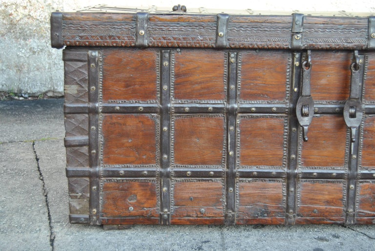 This is a blanket chest from India, made circa 1780. All the metal strapping, handles and lock clasps are handmade of hand-forged iron. There is beautiful hand carving around the bottom edge of the top of the chest. On the right and left front sides