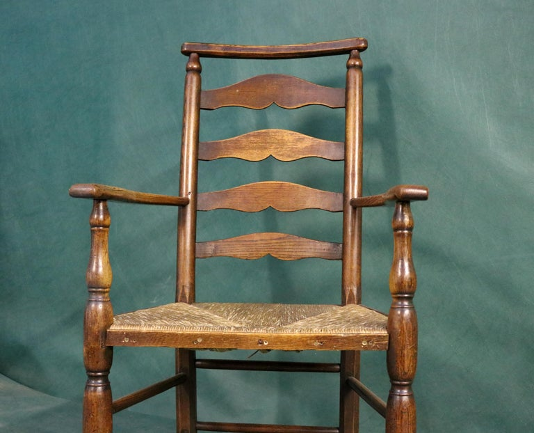 With a ladder back. The legs turned and terminating pad feet. The legs are united by turned spindles.   Measuring: across arms: 60cms height of seat: 43cms height of back: 104cms.