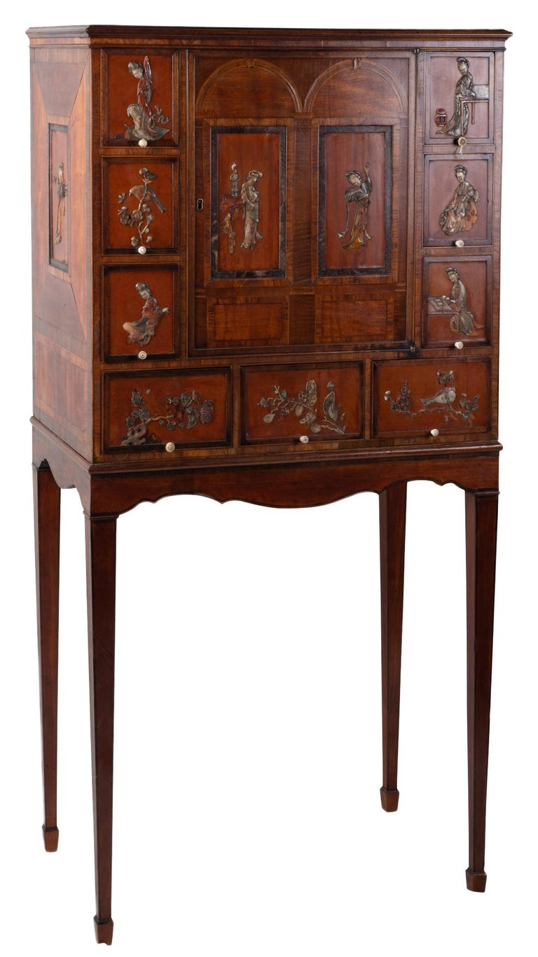 A rare 18th century English satinwood cabinet on stand, having wonderful Kangxi period (1661 until 1722) panels inset to the drawer fronts and doors. Each panel depicting Chinese female courtiers and exotic birds, flowers and butterflies. Mounted on