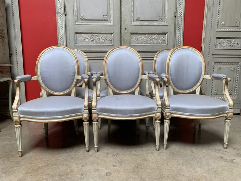 Six French Louis XVI pale gray painted and parcel-gilt dining armchairs from the late 18th century. These fauteuils are beautifully carved with oval backs and flutted legs. The painted and gilt fininsh is recently done, but the frames are of the