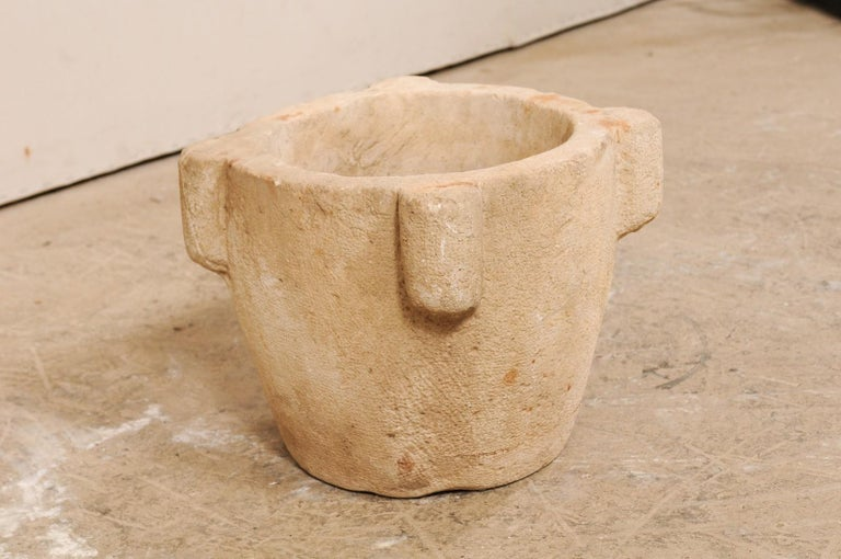 A Spanish hand carved stone mortar from the 18th century. This antique mortar from Spain, once used to grind various ingredients for cooking or medicinal purposes, is nicely sized standing at 14