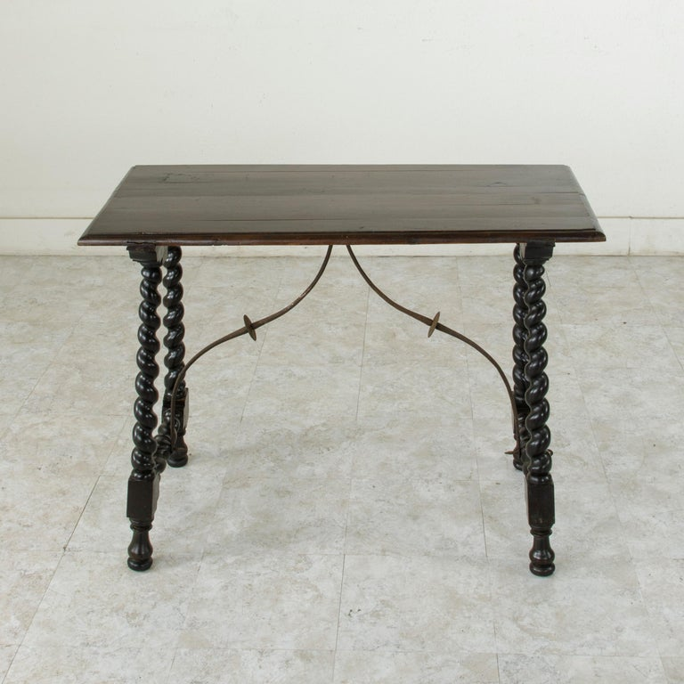 This mid-18th century Renaissance style walnut console table from Spain features hand-turned barley twist legs joined by an iron stretcher that provides additional stability. Its 19th century beveled top joins the hand pegged base by means of a
