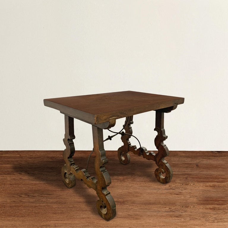 A wonderful petite 18th century Spanish table constructed of walnut and with highly stylized floral carved legs, with two hand-wrought iron stretchers supporting the base. The top has been refinished, but retains the character of the original piece.
