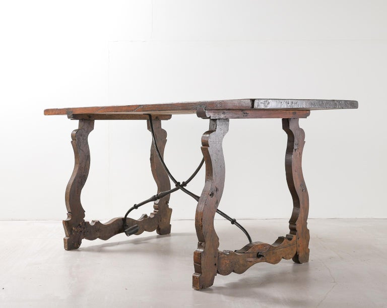 18th century Spanish walnut table with lyre legs and wrought iron supports. Solid walnut plank top connected to the legs by dovetail joints.