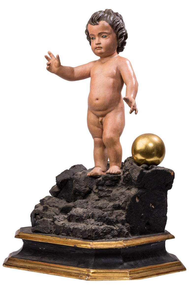 This polychrome wood figure of the Triumphant Infant Jesus was sculpted in Spain in the 18th century, following Andalusian tradition. The inclusion of a golden ball is symbolic of Christ's triumph over the world. 