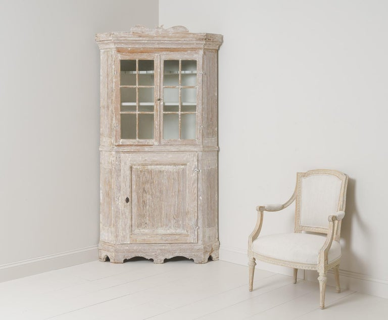 A late Baroque period corner vitrine cabinet from the 18th century in hand-scraped original paint with scalloped base and reeded sides and door. Original lock with key. Original glass. The upper section contains two shelves, the top shaped and