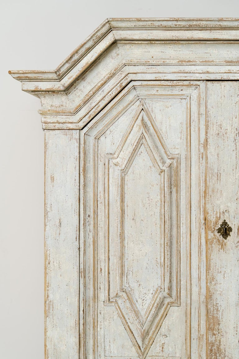 An important and richly carved Swedish armoire or linen press cabinet from the Baroque period with handsome ball feet, circa 1750. The large doors sit above a single drawer and open to reveal three adjustable, internal shelves. This is a rare piece
