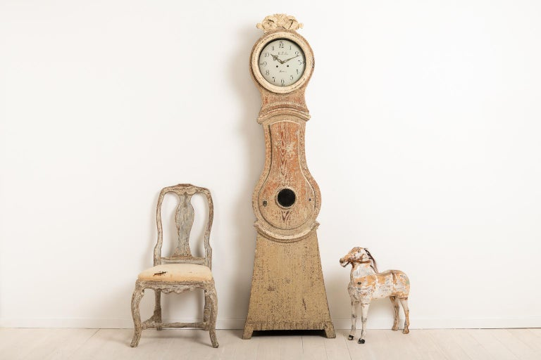 Swedish Gustavian long case clock made circa 1800. The clock is dry scarped to original paint. An unusual detail is the lock on the door which is also in fully working condition. Old original glass in the ring and on the door. Healthy and solid