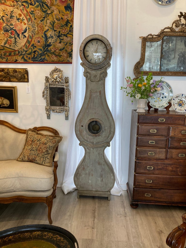 Rare, authentic 18th century Swedish Mora clock, circa 1790. with very graceful serpentine shape and an arresting stance, circular hood with original enamel clock face over scrolling and flared base over charming ogee feet. The face includes a quite
