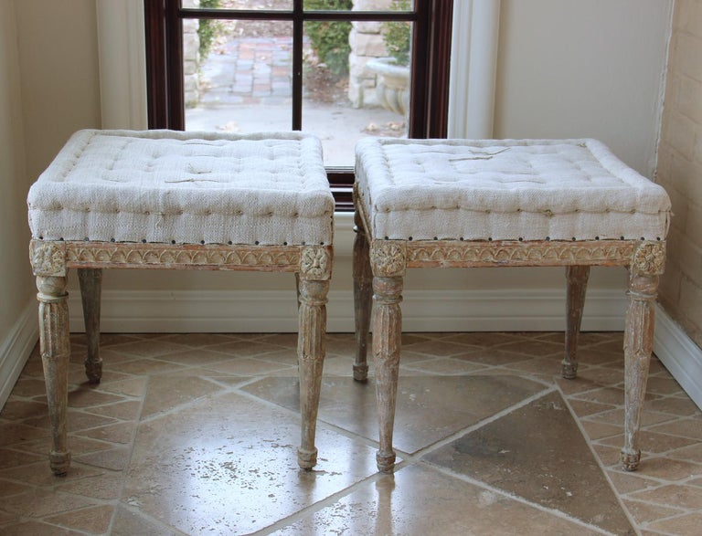 Beautifully carved pair of Swedish benches from the Gustavian period, hand-scraped to reveal the original paint surface and newly upholstered in linen with handstitched tufted seats, circa 1790. There is carved egg and dart detail on the seat frame,