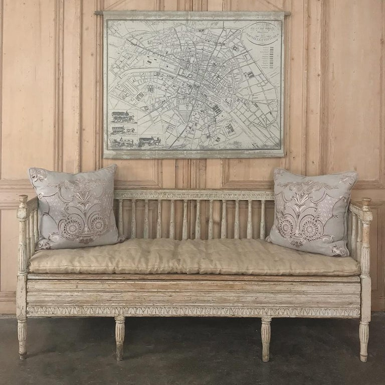 18th century Swedish Gustavian period daybed - hall bench circa 1790 features tailored, neoclassical lines that are definitive of the era, with slat backs surrounding the seating area, and charming rustic carved motifs around the top of the gallery