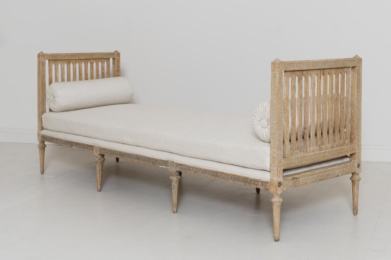 An 18th century Stockholm original daybed by Johan Lindgren (Stockholm 1770-1800). This stunning piece is from the Gustavian period and has been dry scraped to reveal the original paint. Beautiful egg and dart carving detail around the arms and