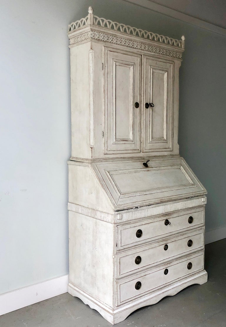 Very fine example of 18th century period Gustavian secretaire with richly carved balcony pediment cornice and fall front desk with multiple small compartments over a Classic three-drawer bureau on beautifully shaped skirt with feet, Sweden, circa