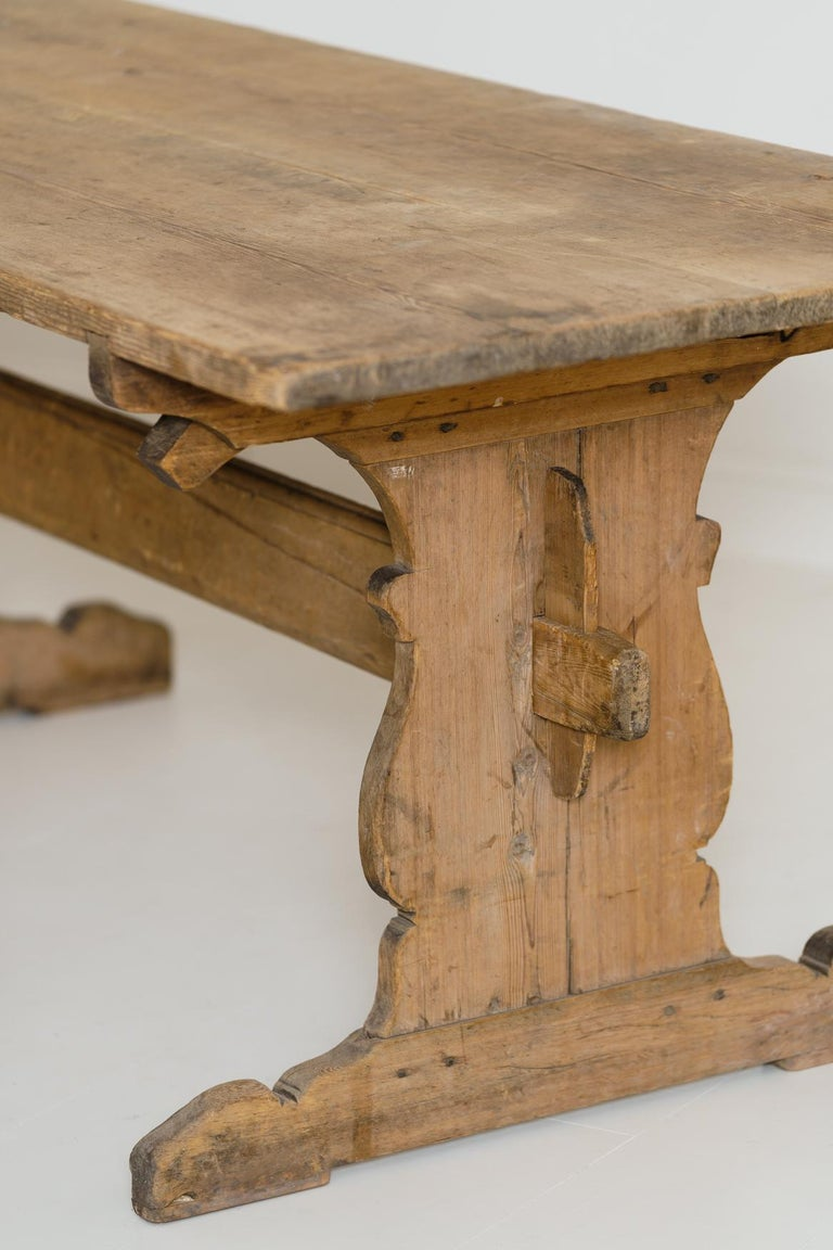 A charming Swedish trestle dining table, circa 1770, with a deep, honey-colored patina. It has a beautiful plank top with central stretcher and shaped sides. This rustic allmoge (countryfolk) table has a time worn, untouched, original patina.