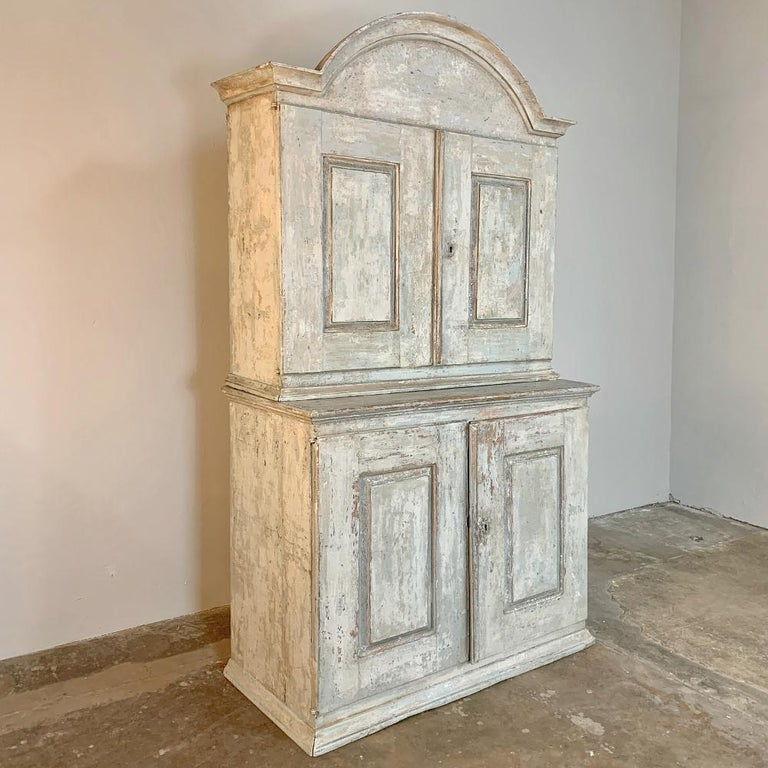 18th century Swedish painted buffet a Deux Corps will add a Gustavian flair to any room, an immediately command attention with its boldly arched crown and lovely patinated and distressed painted finish. Spacious interiors above and below only add to