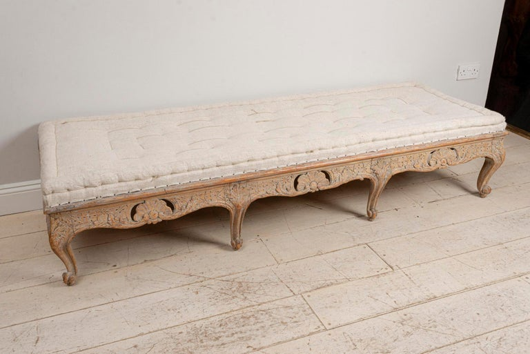 A wonderful bench, coffee table or stool which has carved scrolled decoration to the front and sides which was possibly converted from a sofa at some point in the past. It could also work well as a coffee table or as an interesting statement piece