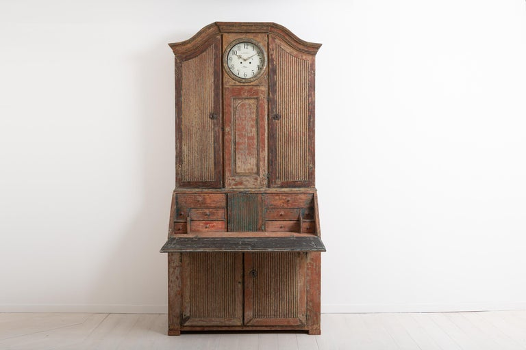 Rococo clock secretary in folk art from northern Sweden. The cabinet - or the secretary - is in two separate pieces and manufactured around the year 1800. It is dry scraped to traces of the original paint and has a rustic patina with natural wear.