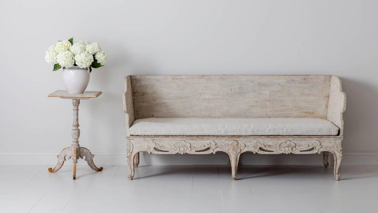 An 18th century Swedish (Tråg sofa) from the Rococo period with original linen seat, back, and side cushions. This is an exceptional and rare period piece that was purchased from a private collection in Belgium. It has been hand-scraped back to