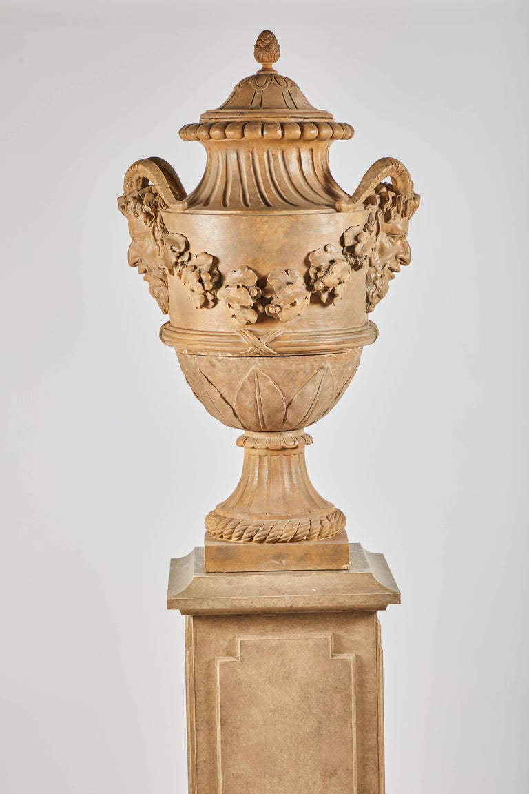 18th century terracotta covered urns on wood pedestals from the collection of Karl Lagerfeld. Extremely well-cast garlands swag between handles in the form of Satyrs.  Measures: 101.5
