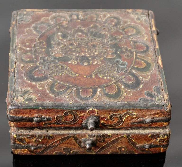 A small and very charming Tibetan covered box constructed with metal straps and painted with thick polychrome paint. The decorative scroll designs culminate into a Buddha or wrathful deity with extended hands encircled by a Lotus flower in ox blood