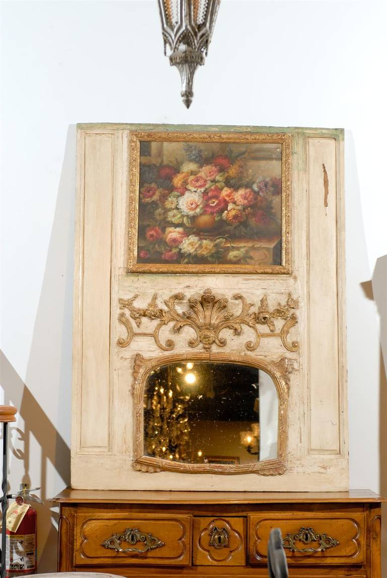 A French Louis XV painted trumeau mirror from the 18th century, with original floral oil painting and carved giltwood motifs. Born in France during the second half of the 18th century, this exquisite trumeau mirror attracts our attention with its