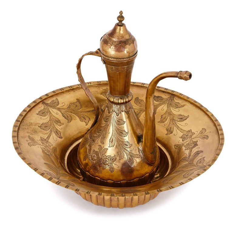 This beautiful ewer and basin set is a delightful product of the 18th century Ottoman Empire, with a striking design aesthetic. It is made from 'tombak', or gilt-copper, a material commonly used in the Ottoman Empire to make precious and ceremonial