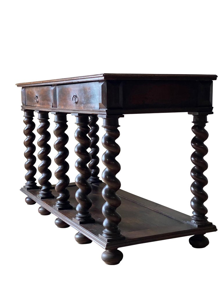 18th century Italian two-drawer walnut console. The console has seven turned legs and a lower tier shelf. Recently refinished.