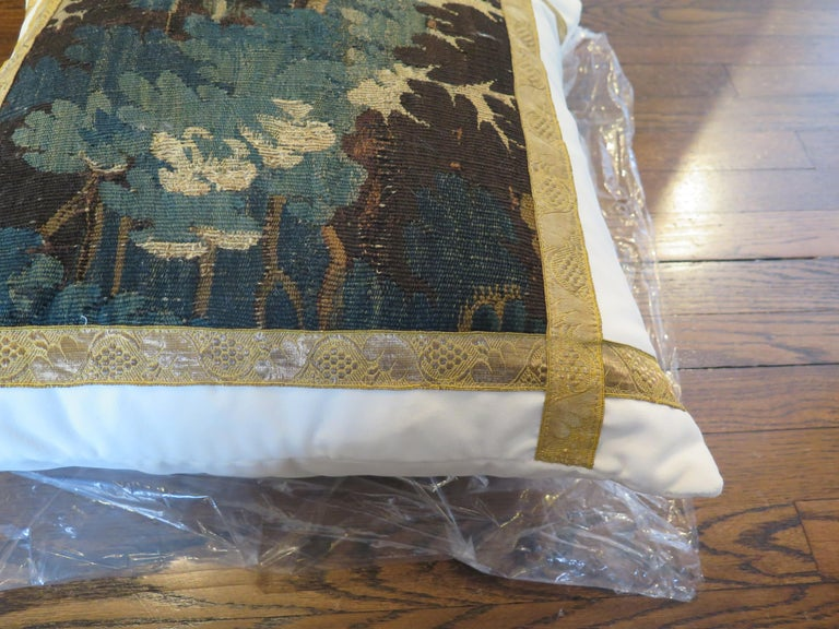 Custom 18th century verdure tapestry pillow adorned with antique French gallon. Pillow is constructed out of Holly Hunt Performance white velvet. Down filled.