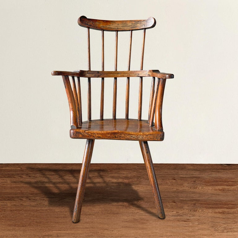 A fantastic 18th century Welsh stick chair with a thick burl walnut seat, unusual heavy front arm supports, traces of the original paint, and a fantastic patina only three hundred years of time can bestow.
