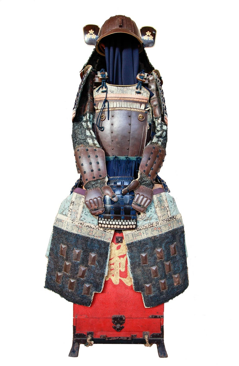"""This beautifully preserved, light-weight Japanese samurai armour was made during the Edo period (1603-1868) and comes with its original inscribed red armour box """"Gusoku-bitsu"""". Its components are connected by rivets and dark blue"""