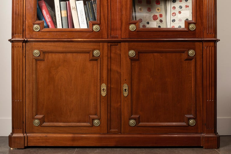 Exceptional mahogany bookcase and mahogany veneer, opening by two glass doors in the upper part and two leaves in the lower part, the pillars are fluted and go up towards the rich cornice, itself fluted and rudentés.  Stamp (middle left) of