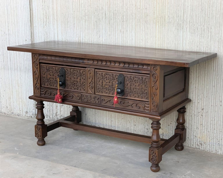 This large Spanish late 18th century features a beautiful one plank rectangular top over two carved drawers. Each drawer, featuring slightly different hardware, is adorned with geometrical motifs. Rosettes are carved between the drawers and each