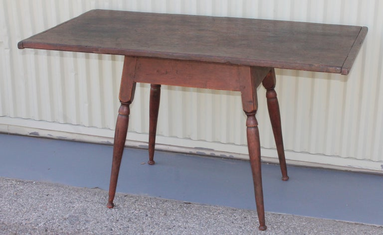 18th century Tavern table from New England in original dark red surface base with a scrub walnut top and bread board ends. This table is square nail and wood peg construction.