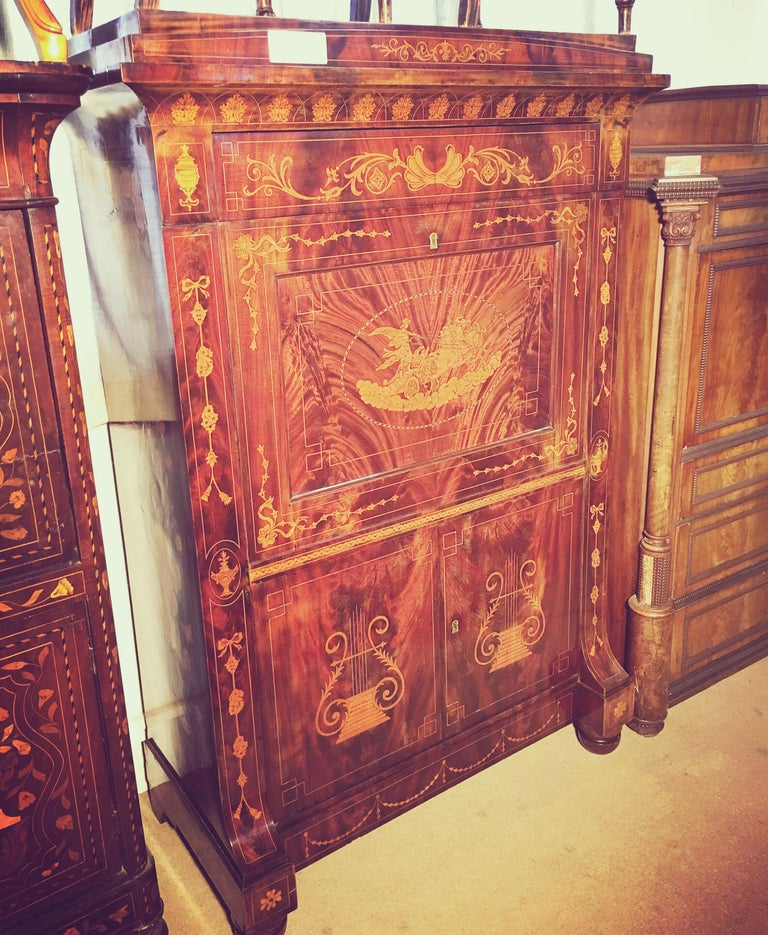 Fantastic Dutch secretaire in mahogany veneer. Rich decoration of inlays with motifs of urns, flower loops and horse carpets. Front with fold-down writing disc, two drawers and door pairs. On the front with an inlay depicting Apollo on the chariot