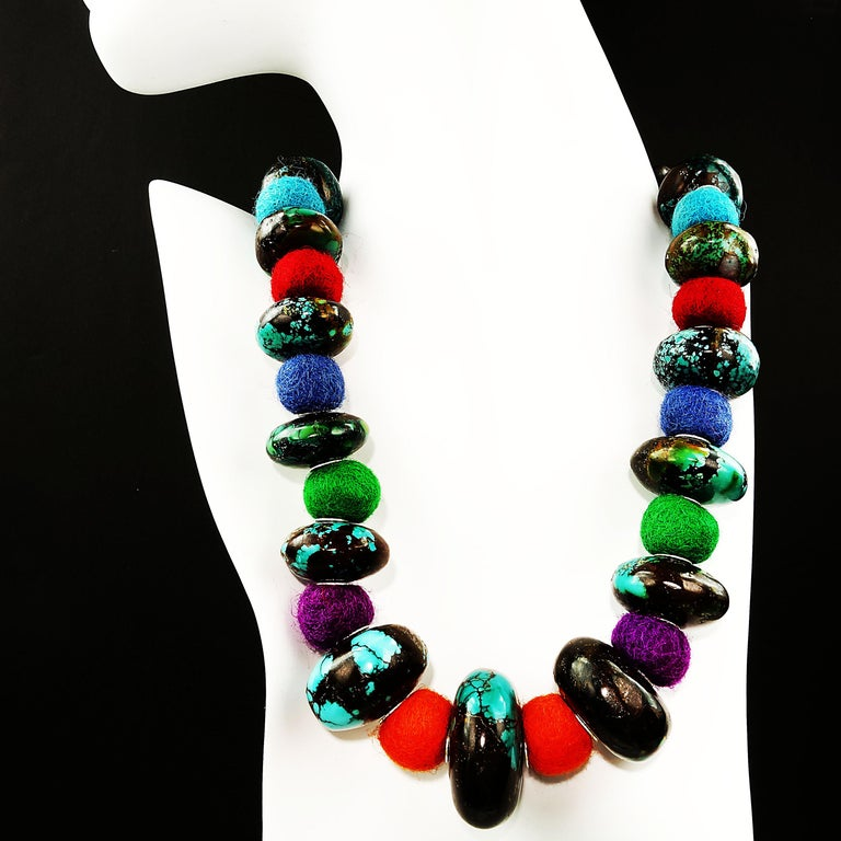 China meets Nepal in this unique necklace of colorful felted wool balls and graduated smooth rondelles of gorgeous Turquoise matrix.  The Turquoise measures 21-33 MM.  The felted wool approximately 14-16 MM.  The entire necklace is secured with a