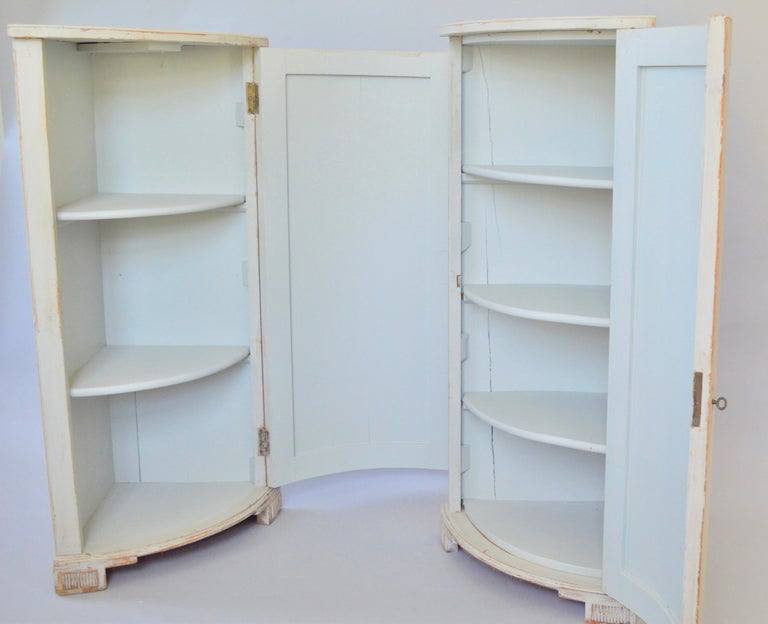 A pair of identical corner cabinets, grisaille grey-blue painted. Richly decorated with hand painted flower urns or vases on the front.