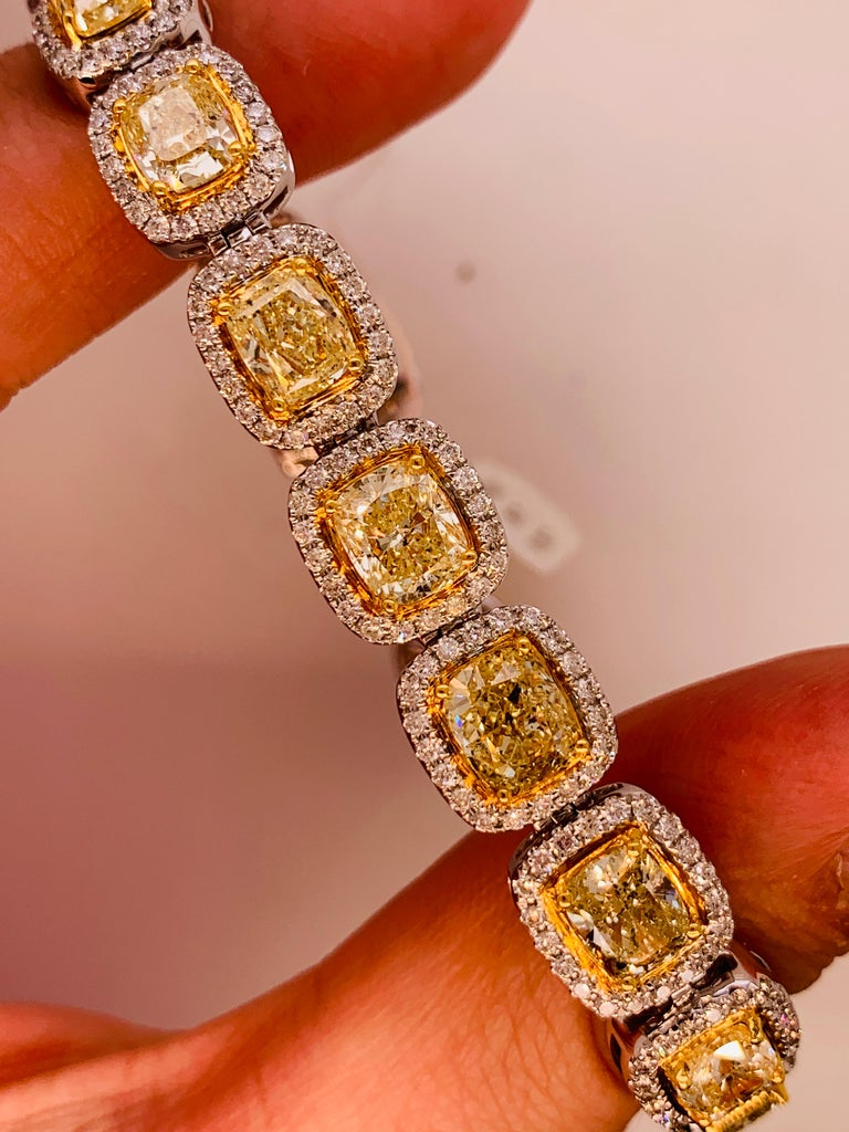 Elegant 18K white and yellow gold, yellow diamond bracelet features Eighteen cushion cut yellow diamonds, totaling 19.00 carats of Yellow diamonds, surrounded by 3.00 carats of white diamonds. Each yellow diamond is over one carat.  7.5