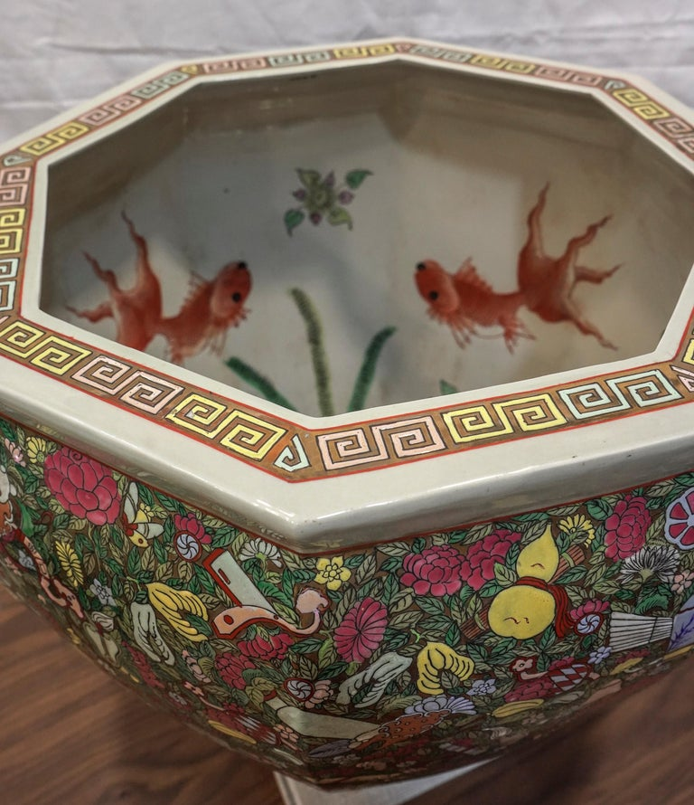 A beautiful Chinese porcelain jardinière, with a floral and porcelain motif using the champleve technique. Painting inside with red fish and seaweed. Octagonal shade, decoration with yellow, green, blue and pink colors on a golden