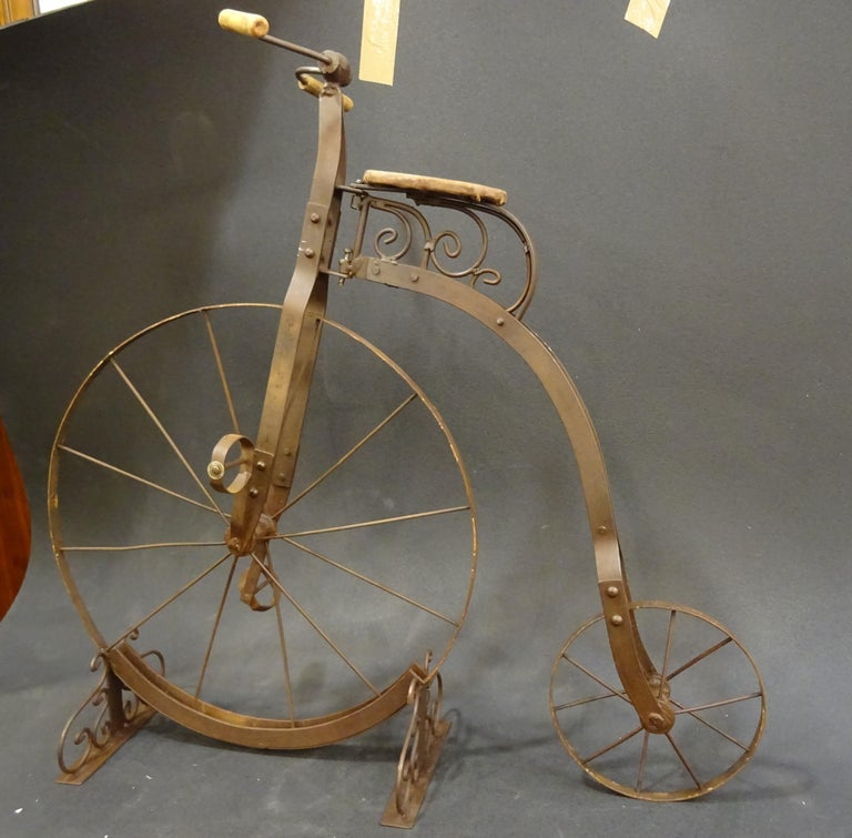 An antique Penny- Farthing bicycle for children from the early 20th century. It is made of twisted iron bars forged and fully bonded togheter by struck rivets. The wheels are made of metal as well without a rubber strip. They are not warped and no
