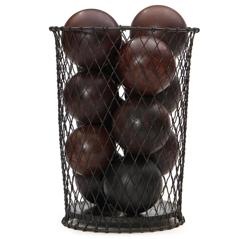 A vintage black patina waste basket well-formed of solid steel wire and woven in a diamond pattern. Filled with 12 lignum vitae bowling balls. Manufactured in the 1920s.